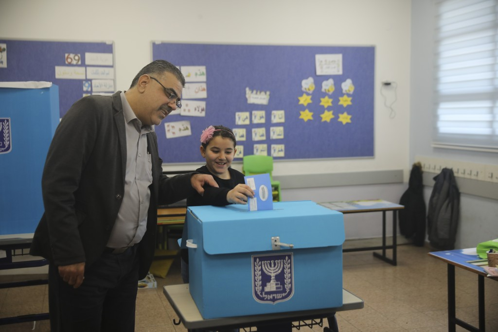 A man and his daughter vote during elections in Tamra, an Arab town in Israel, Monday, March 2, 2020. (AP Photo/Mahmoud Illean)