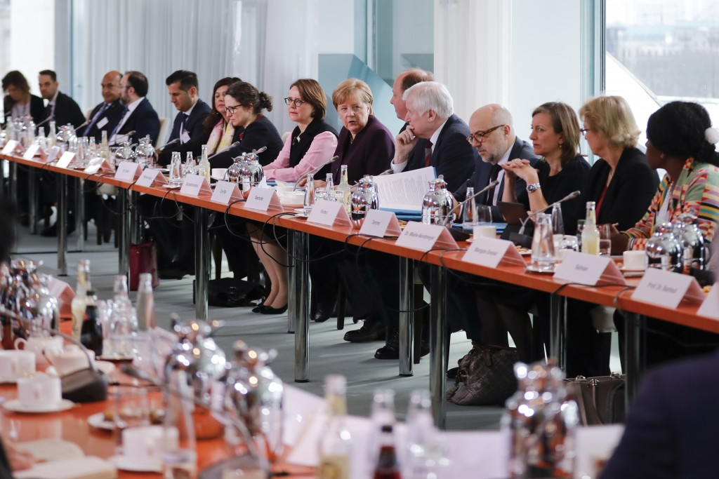 German Chancellor Angela Merkel, seventh right, speaks to media ahead of a meeting with leaders of migrant associations at the chancellery in Berlin, ...