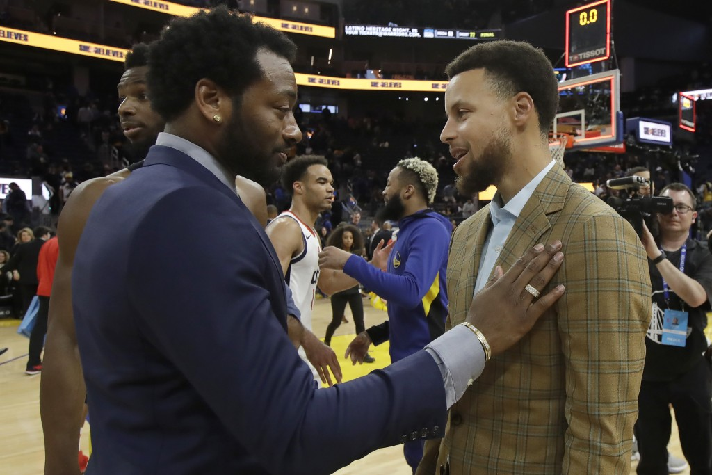 Injured Washington Wizards guard John Wall, left, talks with injured Golden State Warriors guard Stephen Curry after the Wizards beat the Warriors in ...