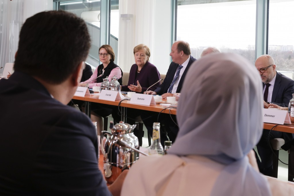 German Chancellor Angela Merkel, center, speaks to media ahead of a meeting with leaders of migrant associations at the chancellery in Berlin, Germany...
