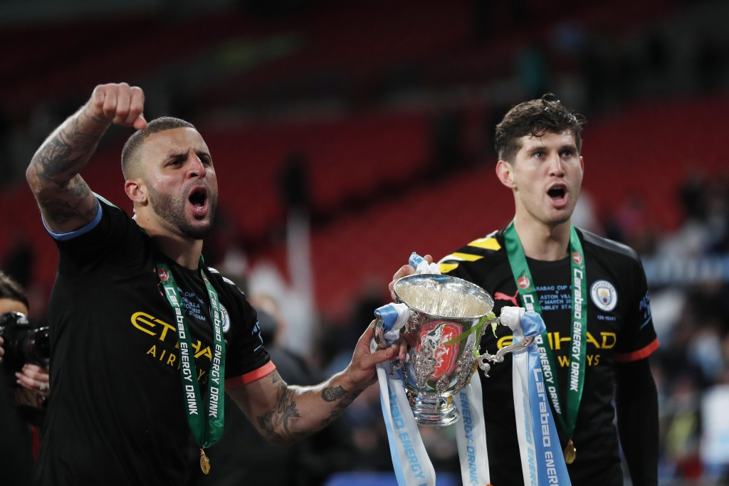 Manchester City's Kyle Walker, left, holds the trophy with his teammate Manchester City's John Stones after winning the English League Cup Final socce...