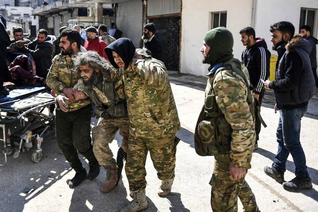 In this photo taken on Sunday, March 1, 2020, Turkey-backed opposition fighters help a fellow fighter wounded in fighting with Syrian government force...
