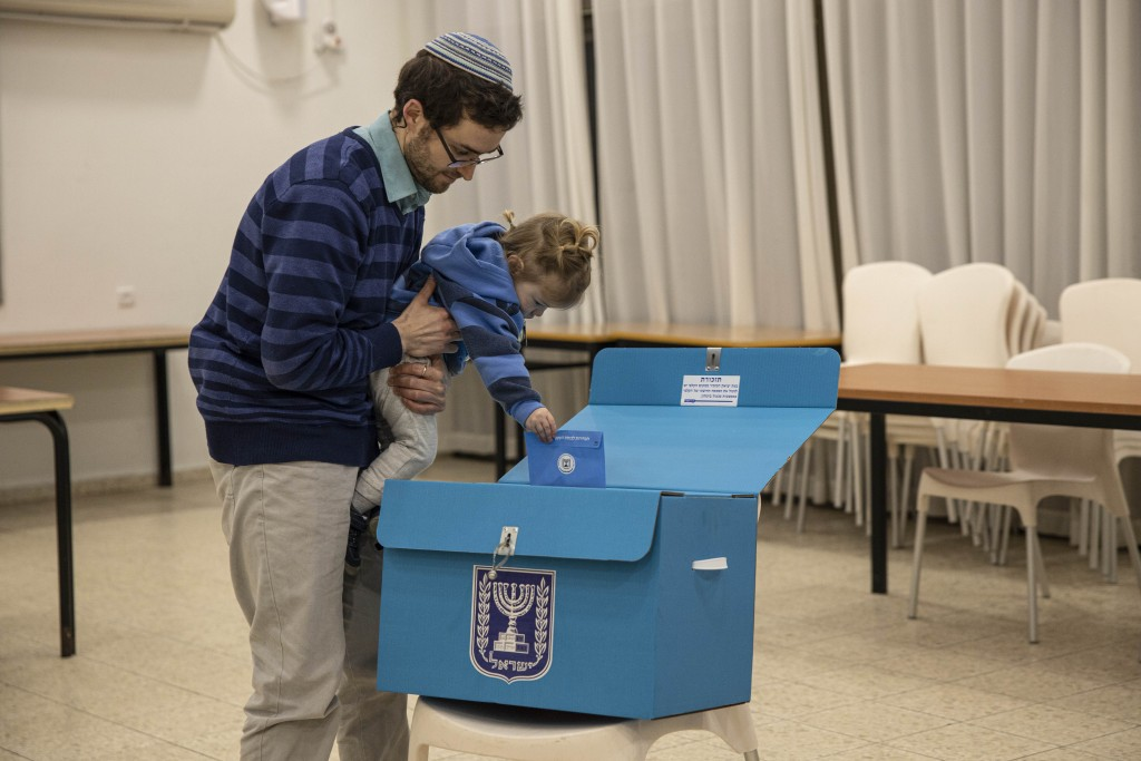 An Israeli settler casts a vote with his son during elections in the settlement of Alon Shvut, West Bank, Monday, March 2, 2020. (AP Photo/Tsafrir Aba...