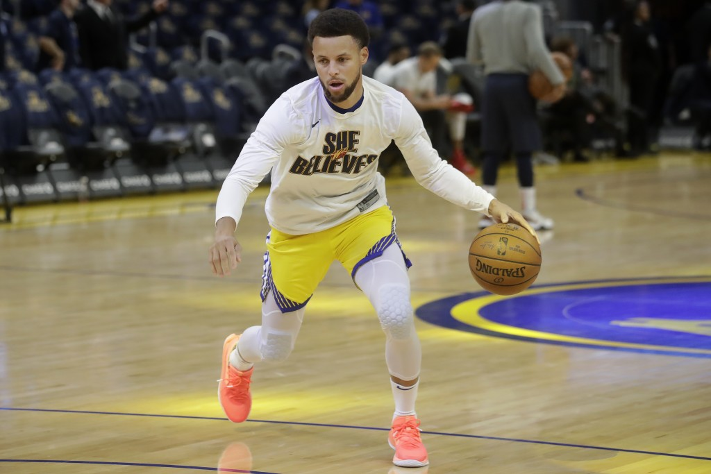 Injured Golden State Warriors guard Stephen Curry warms up before his team's NBA basketball game against the Washington Wizards in San Francisco, Sund...