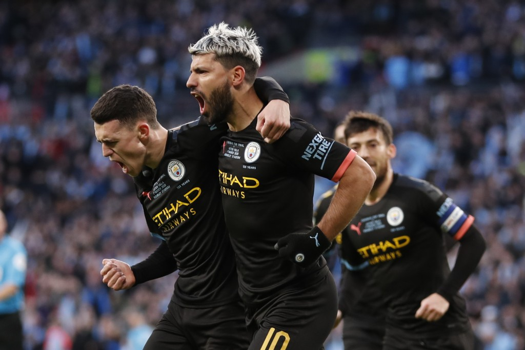 Manchester City's Sergio Aguero, right, celebrates with his teammate Phil Foden after scoring his side's first goal during the League Cup soccer match...