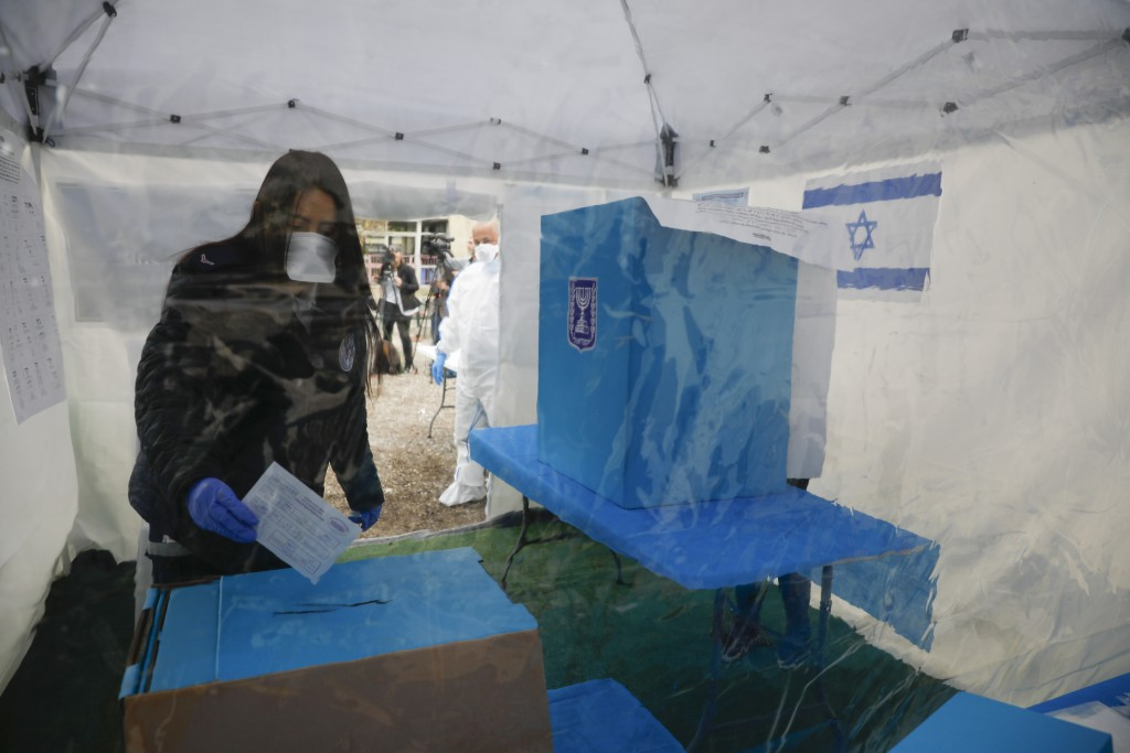 A woman quarantined for Corona virus votes in a specially set up tent in Tel Aviv, Israel, Monday, March 2, 2020. (AP Photo/Ariel Schalit)