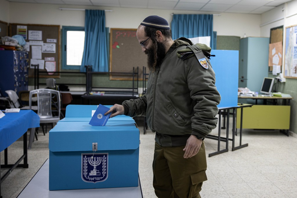 Israeli soldier casts his vote during elections in the settlement of Efrata, West Bank, Monday, March 2, 2020. (AP Photo/Tsafrir Abayov)