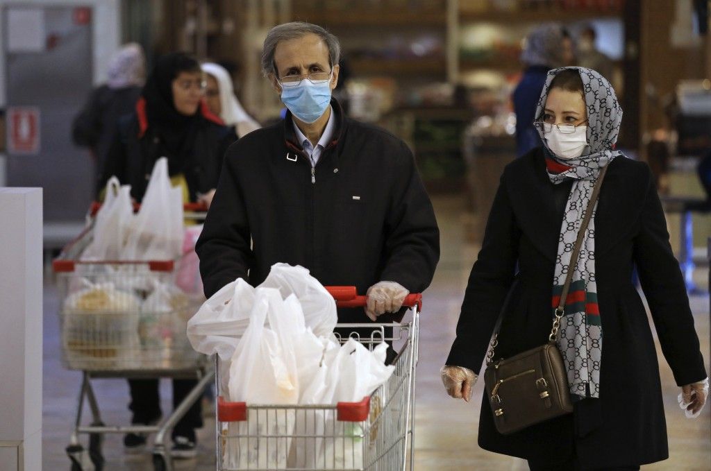 Shoppers wearing face masks and gloves shop at the Palladium Shopping Center, in northern Tehran, Iran, Tuesday, March 3, 2020. Iran's supreme leader ...