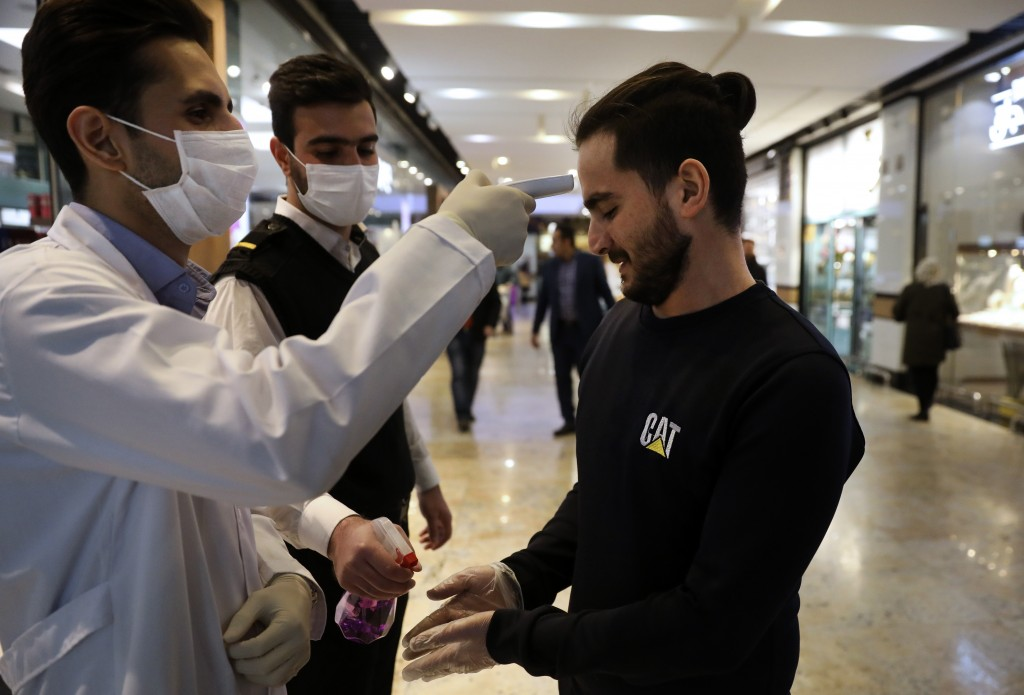 A man has his temperature checked and his hands disinfected as he enters the Palladium Shopping Center, in northern Tehran, Iran, Tuesday, March 3, 20...