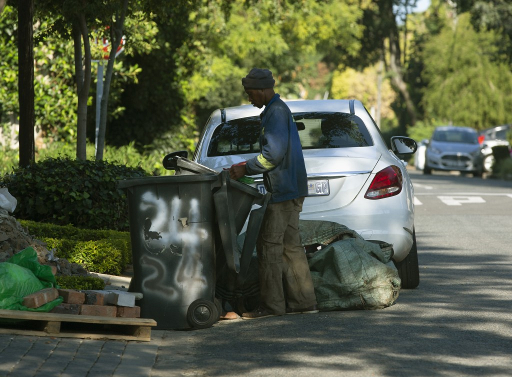 In this photo taken Wednesday, Feb. 26, 2020 a man looks for recyclable materials to make money in a Johannesburg suburb. Official statistics released...