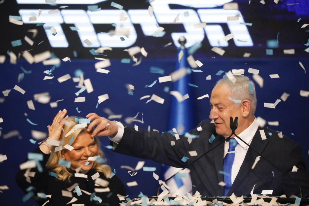 Israeli Prime Minister Benjamin Netanyahu, accompanied by his wife Sara, addresses his supporters after first exit poll results for the Israeli electi...