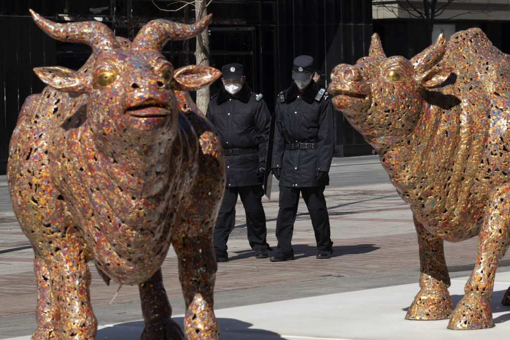 Security personnel walk past bull sculptures depicting prosperity along a retail street in Beijing on Tuesday, March 3, 2020. Asian shares rose Tuesda...