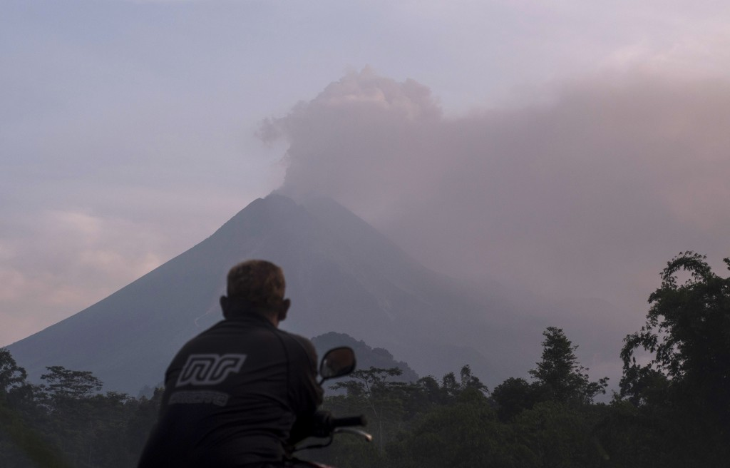 A man watches as Mount Merapi spews volcanic material into the air in Sleman, Indonesia, Tuesday, March 3, 2020. Indonesia's most active volcano erupt...