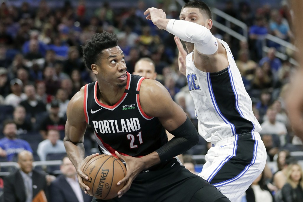 Portland Trail Blazers center Hassan Whiteside (21) looks to pass the ball while covered by Orlando Magic center Nikola Vucevic, right, during the fir...