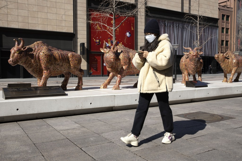 A woman wearing a mask walks past bull sculptures depicting prosperity along a retail street in Beijing on Tuesday, March 3, 2020. Asian shares rose T...