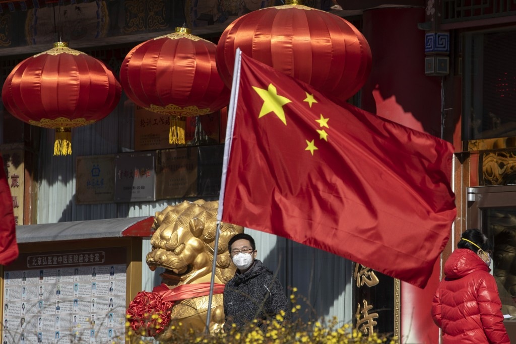 A masked man looks out near a national flag outside a traditional medicine hospital in Beijing on Tuesday, March 3, 2020. Mushrooming outbreaks in the...