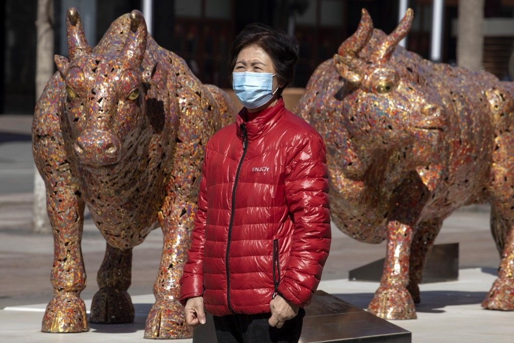 A woman wearing a mask stands near bull sculptures depicting prosperity along a retail street in Beijing on Tuesday, March 3, 2020. Asian shares rose ...