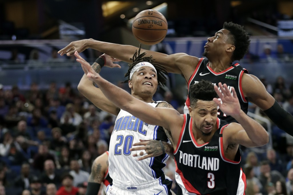 Orlando Magic guard Markelle Fultz (20) passes the ball behind his head as he gets trapped between Portland Trail Blazers center Hassan Whiteside, bac...
