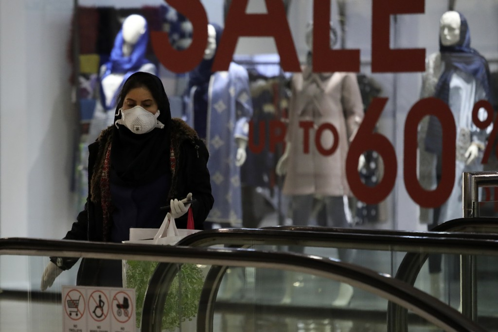 A woman wearing face mask and gloves shops at the Palladium Shopping Center, in northern Tehran, Iran, Tuesday, March 3, 2020. Iran's supreme leader p...