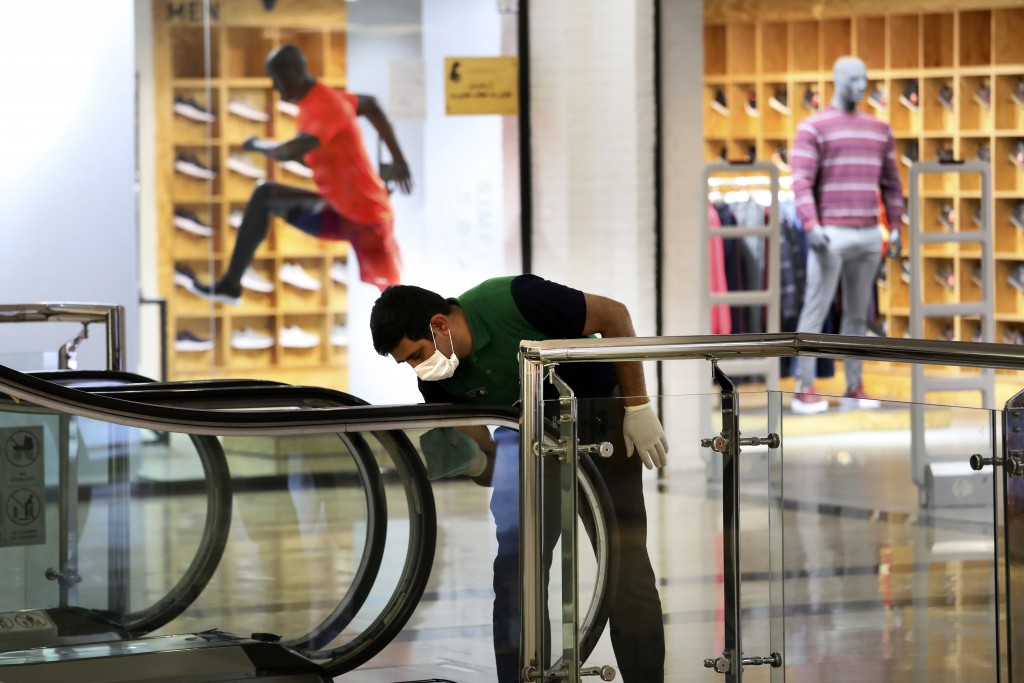 A worker wearing a face mask cleans and disinfects an escalator against coronavirus at the Palladium Shopping Center, in northern Tehran, Iran, Tuesda...