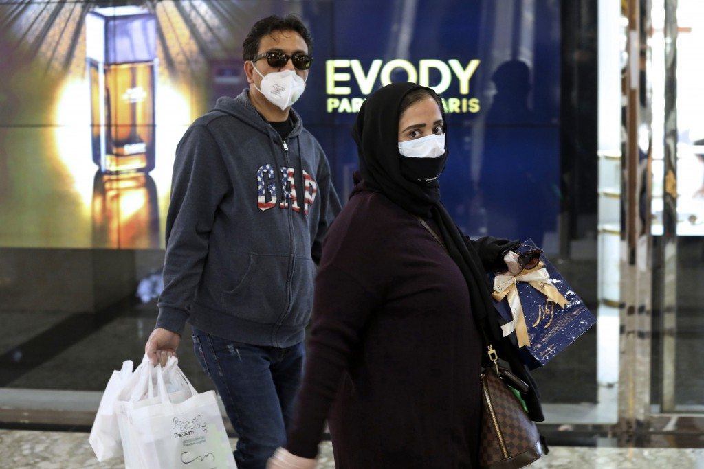 People wearing face masks and gloves shop at the Palladium Shopping Center, in northern Tehran, Iran, Tuesday, March 3, 2020. Iran's supreme leader pu...