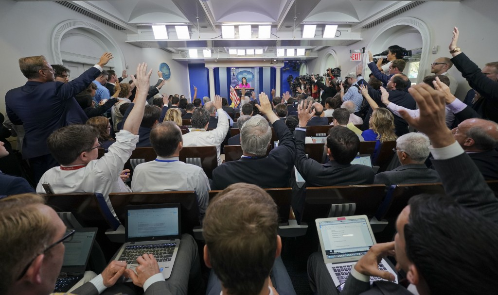 FILE - Oct. 10, 2017, file photo, journalists raise their hands in the White House press room during the daily briefing, in Washington. China is denou...