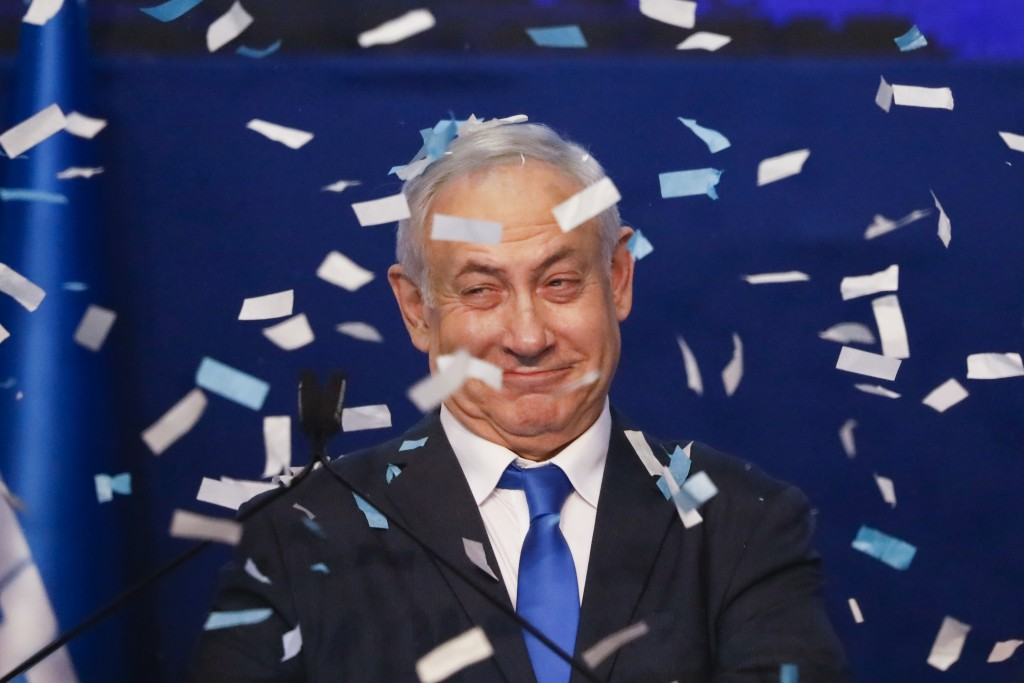 Israeli Prime Minister Benjamin Netanyahu smiles after first exit poll results for the Israeli elections at his party's headquarters in Tel Aviv, Isra...