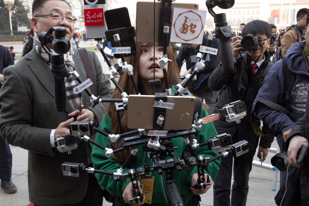 FILE - In this file photo taken Friday, March 3, 2017, a Chinese journalist operates a harness with multiple recording devices capable of recording an...