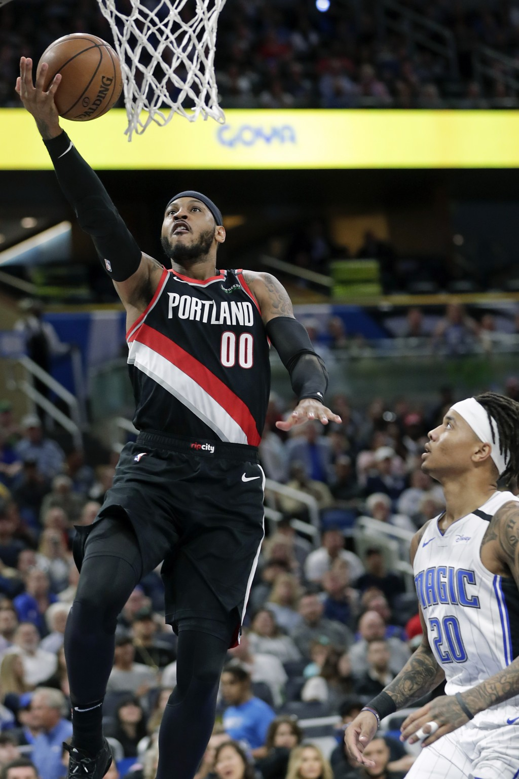 Portland Trail Blazers forward Carmelo Anthony (00) shoots in front of Orlando Magic guard Markelle Fultz (20) during the first half of an NBA basketb...
