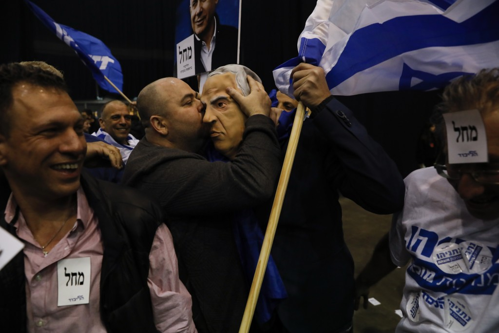 Israeli Prime Minister Benjamin Netanyahu's supporters celebrate first exit poll results for the Israeli elections at his party's headquarters in Tel ...