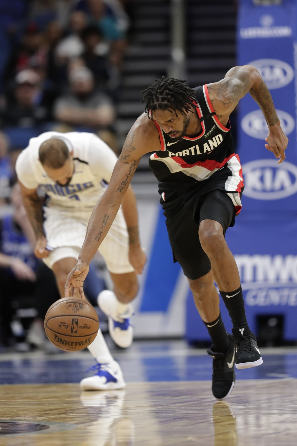 Portland Trail Blazers forward Trevor Ariza, right, scoops up the ball in front of Orlando Magic guard Evan Fournier during the first half of an NBA b...