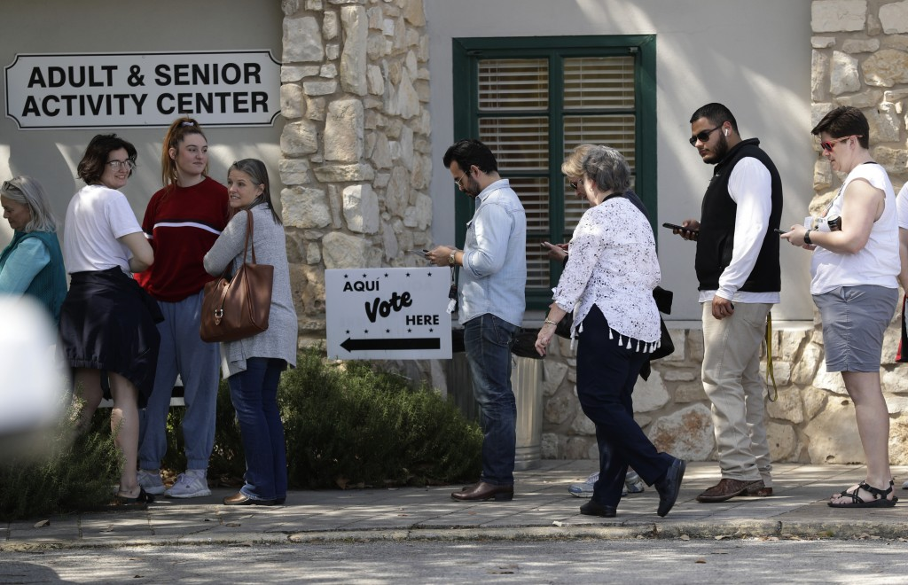 In this Friday, Feb. 28, 2020 photo, voters wait in line at an early polling site in San Antonio. California and Texas are the most populous states in...