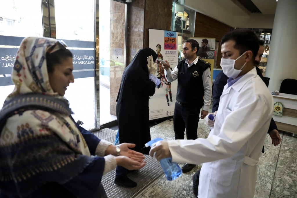 People have their temperature checked and their hands disinfected as they enter the Palladium Shopping Center, in northern Tehran, Iran, Tuesday, Marc...