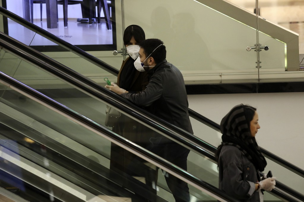 People wearing face masks and gloves ride an escalator at the Palladium Shopping Center, in northern Tehran, Iran, Tuesday, March 3, 2020. Iran's supr...