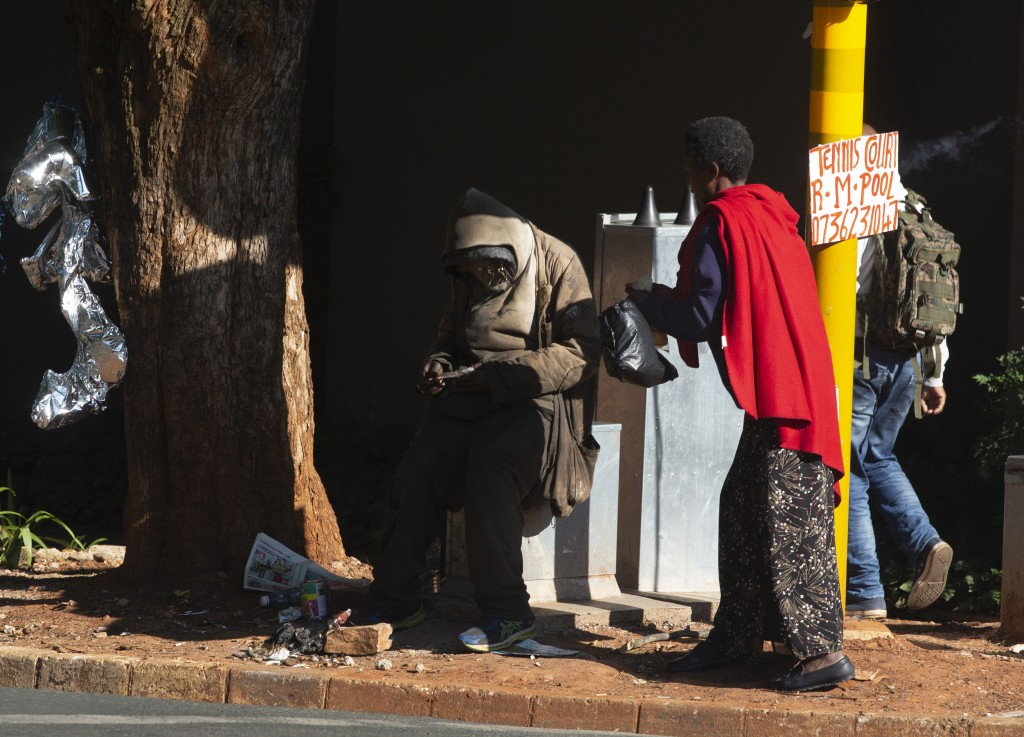 In this photo taken Wednesday, Feb. 26, 2020 a woman talks with a homeless man at a busy Johannesburg intersection. Official statistics released Tuesd...