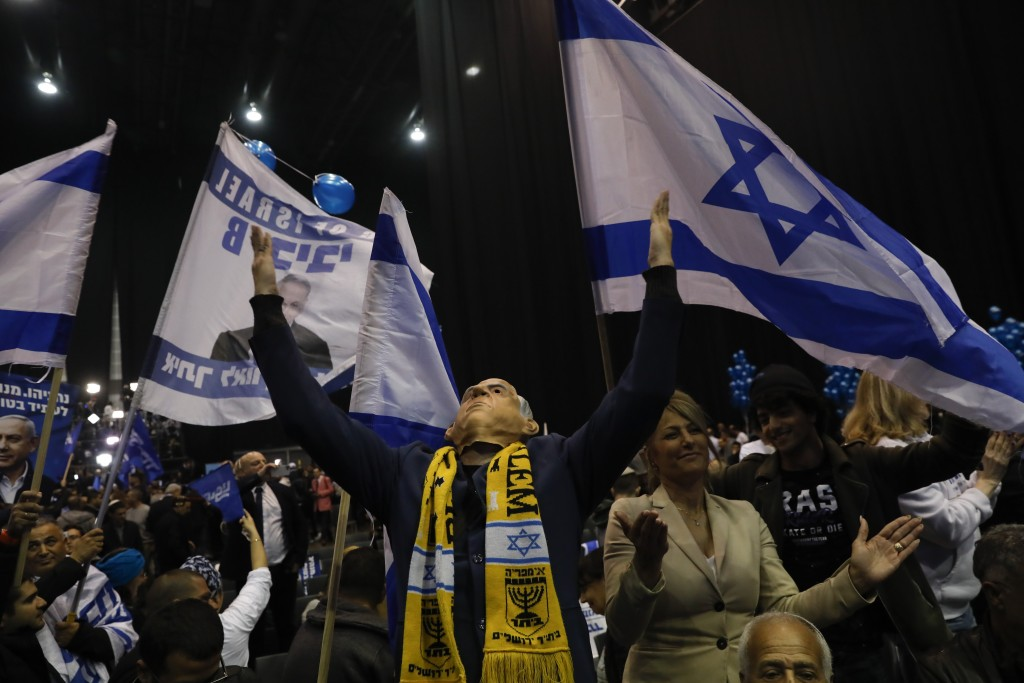 A supporter of Israeli Prime Minister Benjamin Netanyahu wear mask with his likeness as they celebrate first exit poll results for the Israeli electio...