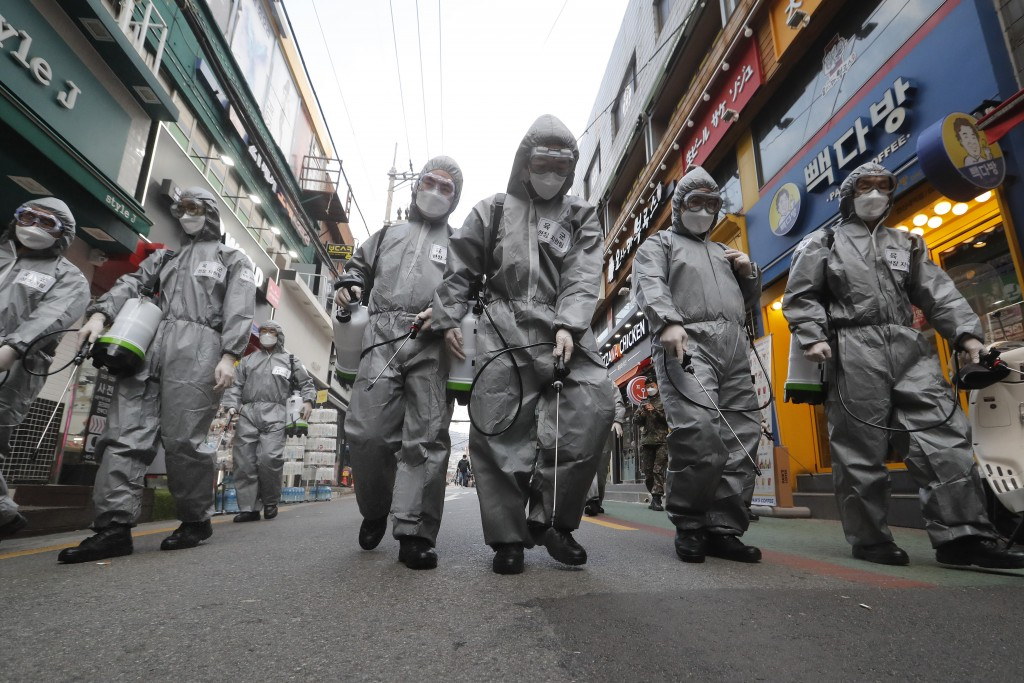 South Korean army soldiers wearing protective gears spray disinfectant as a precaution against the new coronavirus at a shopping street in Seoul, Sout...