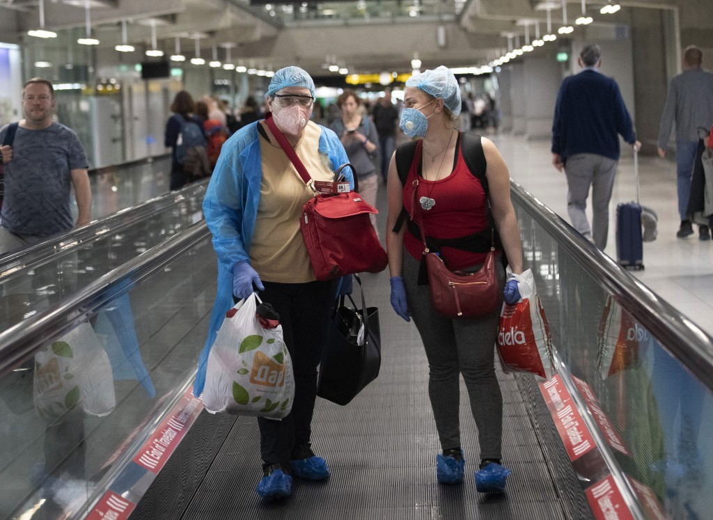 Tourists wearing protective gear against the Covid-19 virus arrive at the Suvarnabhumi Airport  in Bangkok, Thailand, Wednesday, March 4, 2020. (AP Ph...