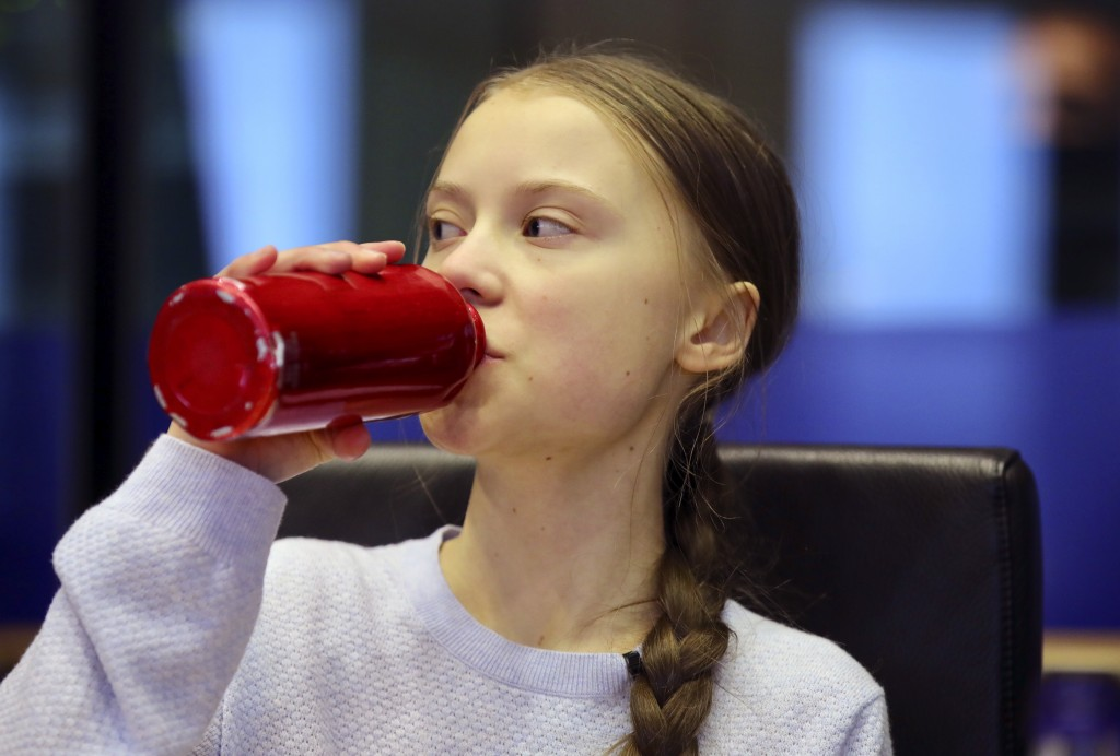 Swedish climate activist Greta Thunberg drinks from her re-usable bottle during a meeting of the Environment Council at the European Parliament in Bru...