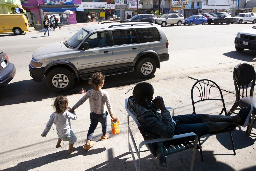 In this Feb. 7, 2020, image, an African seeking asylum sits in front of his apartment in Tijuana, Mexico, as two children pass.  Many countries in Nor...