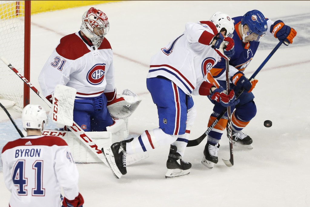 Montreal Canadiens defenseman Xavier Ouellet (61) defends against New York Islanders center Jean-Gabriel Pageau (44) in front of goalie Carey Price du...