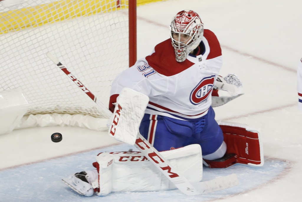 Montreal Canadiens goaltender Carey Price turns the puck away during the second period of the team's NHL hockey game against the New York Islanders, T...