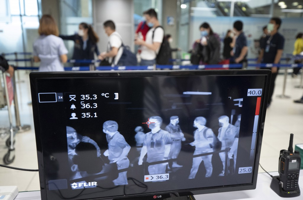 Tourists walk in front of a thermal scanner to check body temperatures as they arrive at the Suvarnabhumi Airport in Bangkok, Thailand, Wednesday, Mar...