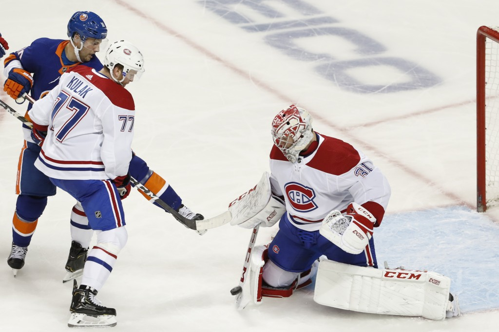 Montreal Canadiens goaltender Carey Price (31) makes a save with defenseman Brett Kulak (77) fending off New York Islanders center Derick Brassard in ...