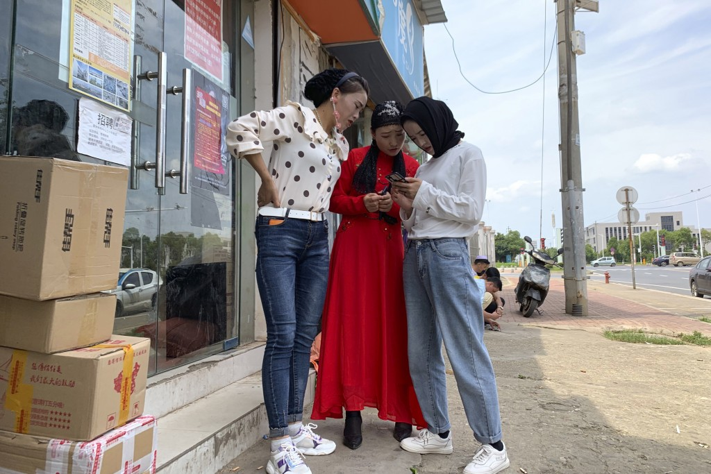 In this June 5, 2019, photo, women from the the Hui Muslim ethnic minority from a nearby neighborhood gather outside a shop near an OFILM factory in N...