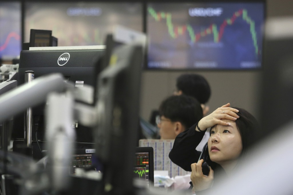 A currency trader watches monitors at the foreign exchange dealing room of the KEB Hana Bank headquarters in Seoul, South Korea, Thursday, March 5, 20...