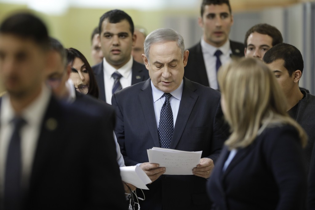 Israeli Prime Minister Benjamin Netanyahu reads from his notes as he walks to a meeting with his nationalist allies and his Likud party members at the...