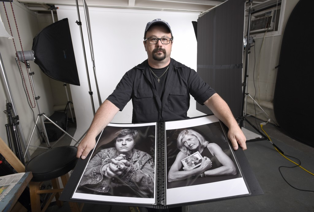 FILE - In this June 21, 2019, file photo, Paul W. Gillespie, a photojournalist at the Capital Gazette newspaper, holds a book of portraits he photogra...