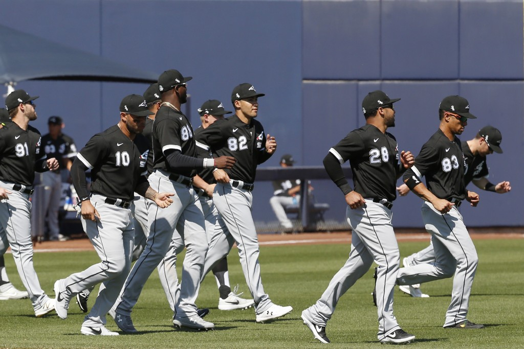 Chicago White Sox players warm up before a spring training baseball game against the Milwaukee Brewers, Wednesday, March 4, 2020, in Phoenix, Ariz. (A...