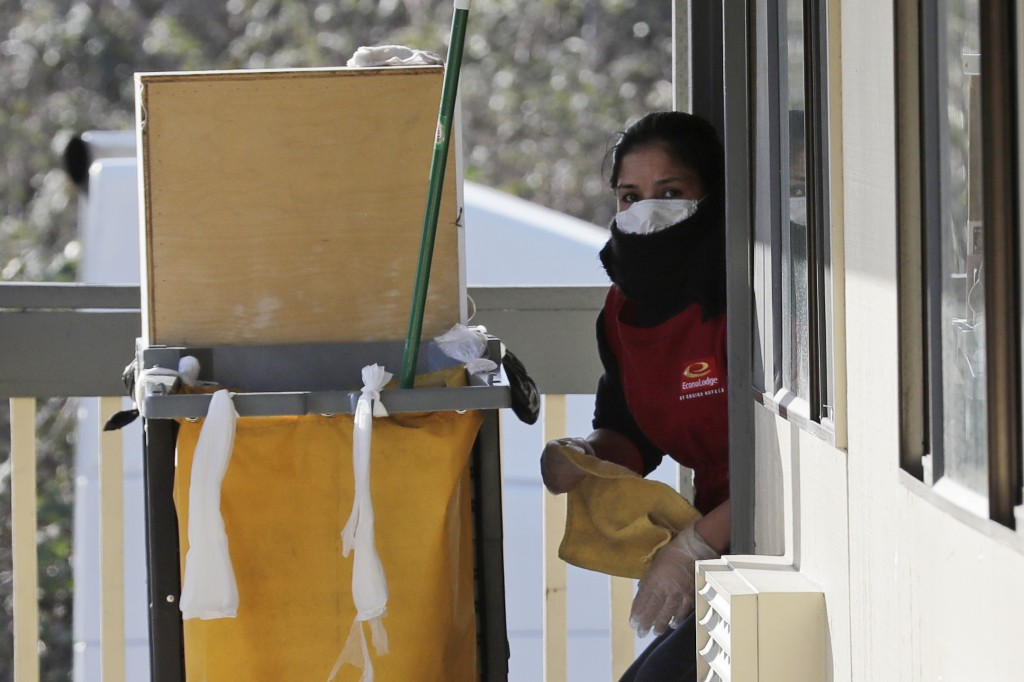A housekeeping worker wears a mask as she cleans a room, Wednesday, March 4, 2020, at an Econo Lodge motel in Kent, Wash. King County Executive Dow Co...